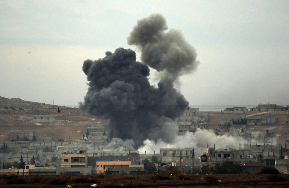 Thick smoke rises following an airstrike by the US-led coalition in Kobani, Syria while fighting continued between Syrian Kurds and the militants of Islamic State group, as seen from Mursitpinar on the outskirts of Suruc, at the Turkey-Syria border, Tuesday, Oct. 14, 2014. Kobani, also known as Ayn Arab, and its surrounding areas, has been under assault by extremists of the Islamic State group since mid-September and is being defended by Kurdish fighters. (AP Photo/Lefteris Pitarakis)