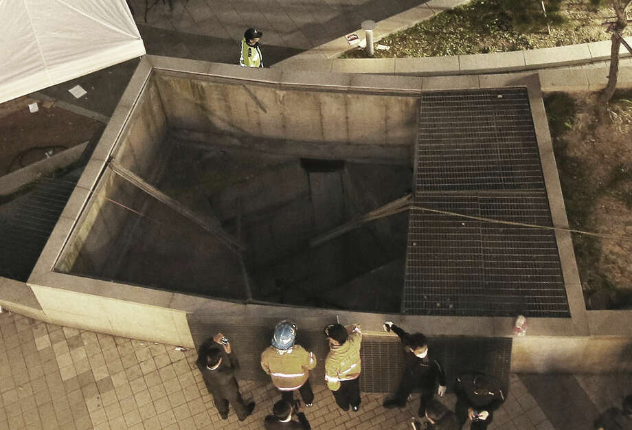 Rescue workers stand around a collapsed ventilation grate at an outdoor theater in Seongnam, south of Seoul, South Korea, Friday, Oct. 17, 2014. Fourteen people were feared dead Friday after the ventilation grate collapsed during a concert by popular girls' band 4Minute, officials said. (AP Photo/Yonhap, Shin Young-geun) KOREA OUT