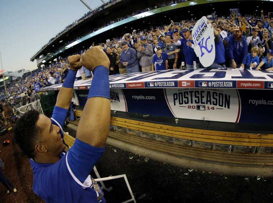 Kansas City Royals' Salvador Perez with fans after the Royals defeated the Baltimore Orioles to win the American League baseball championship series Wednesday, Oct. 15, 2014, in Kansas City, Mo. The Royals advance to the World Series. (AP Photo/Charlie Riedel)