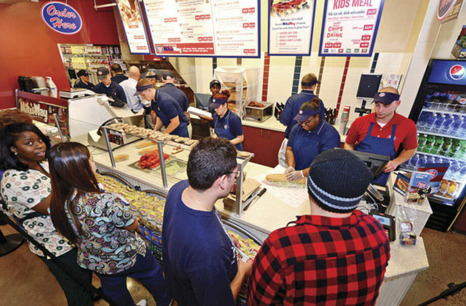 Hour photo / Erik Trautmann Customers line up for sandwiches during the grand opening of Jersey Mike's on CT Ave in Norwalk Wednesday. The store is giving away 10,000 sandwiches in exchange for $1 donations to the CT Sports Foundation to help fight cancer.