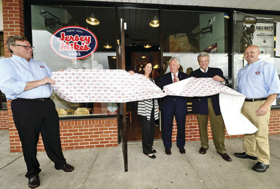 Hour photo / Erik Trautmann Co-owner Brian O'Hagan, CT Sports Foundation Executive Director Jane Ellis, Norwalk Mayor Harry Rilling, CT Sports Foundation founder and baseball great John Ellis and co-owner Troy Davidson help cut the ribbon during the grand opening of Jersey Mike's on CT Ave in Norwalk Wednesday. The store is giving away 10,000 sandwiches in exchange for $1 donations to the CT Sports Foundation to help fight cancer.