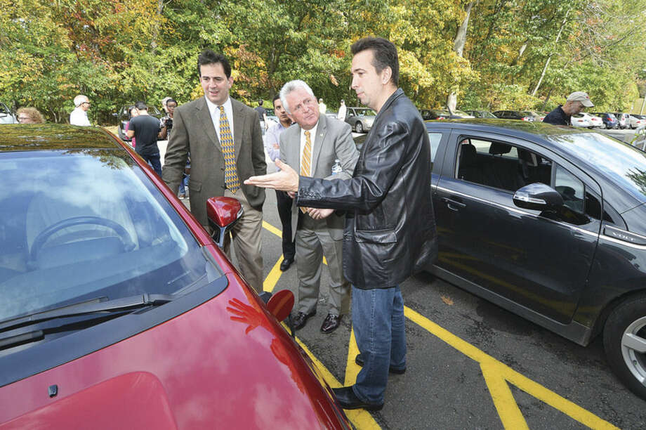 Hour photo/Alex von KleydorffNorwalk Community College opens its new Electric Vehicle Charging Station and graduate Andrew Baumer, who secured the grant, shows Chris Perone and Mayor Harry Rilling how his Chevy Volt plugs in.