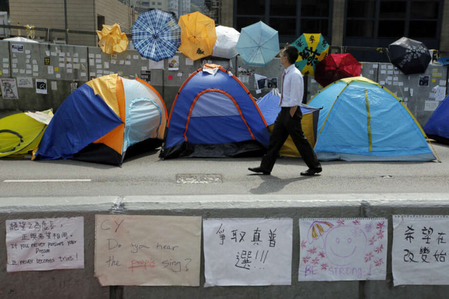 A man walks past tents and umbrellas set up by pro-democracy protesters at an occupied area near the government headquarters in Hong Kong Thursday, Oct. 16, 2014. Hong Kong Chief Executive Leung Chun-ying said Thursday he is ready to start talks as soon as next week with student leaders of the pro-democracy protests that have rocked the city for nearly three weeks. (AP Photo/Vincent Yu)
