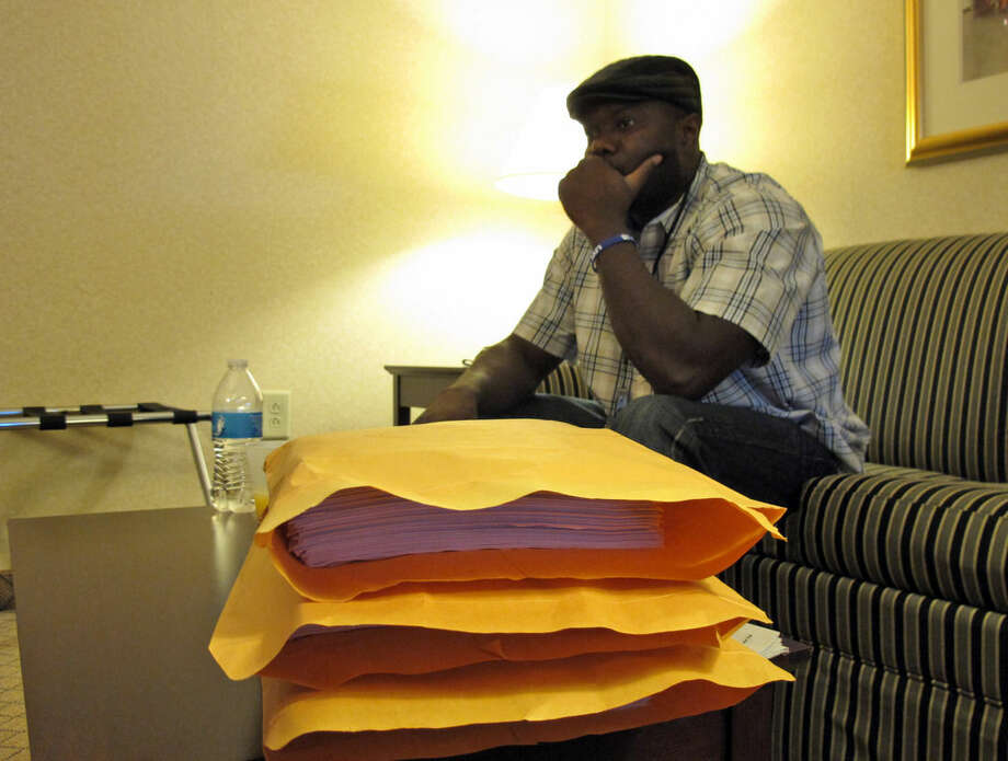 Josephus Weeks, nephew of ebola patient Thomas Eric Duncan who died earlier this week in Dallas, sits behind a stack of medical documents in a hotel room, Friday, Oct. 10, 2014, in Kannapolis, N.C. Duncan's temperature spiked to 103 degrees during the hours of his initial visit to an emergency room; a fever that was flagged with an exclamation point in the hospital's record-keeping system, his medical records show. (AP Photo/Allen G. Breed)