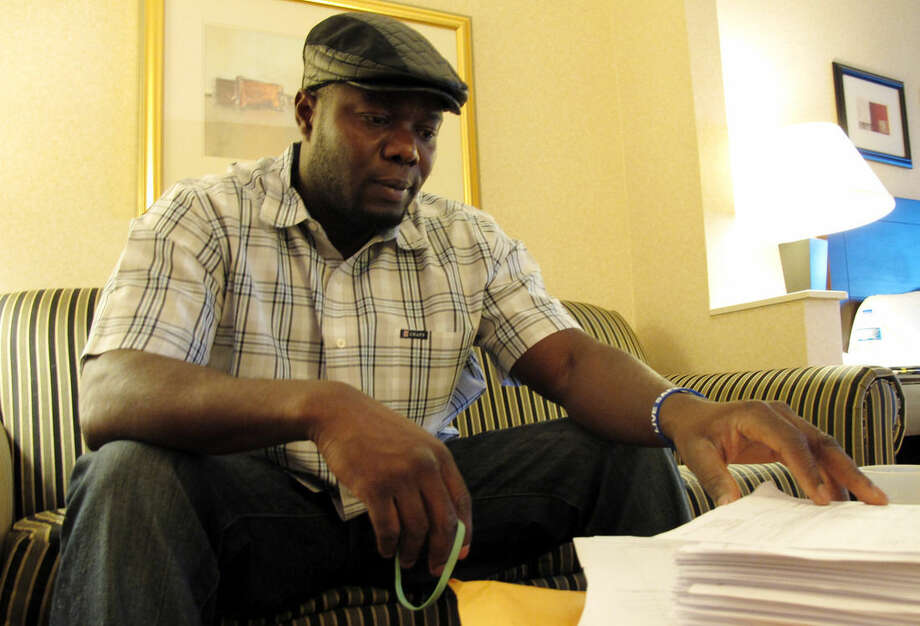 Josephus Weeks, nephew of ebola patient Thomas Eric Duncan who died earlier this week in Dallas, looks through hundreds of pages of medical documents in a hotel room Friday, Oct. 10, 2014, in Kannapolis, N.C. Duncan's temperature spiked to 103 degrees during the hours of his initial visit to an emergency room; a fever that was flagged with an exclamation point in the hospital's record-keeping system, his medical records show. (AP Photo/Allen G. Breed)