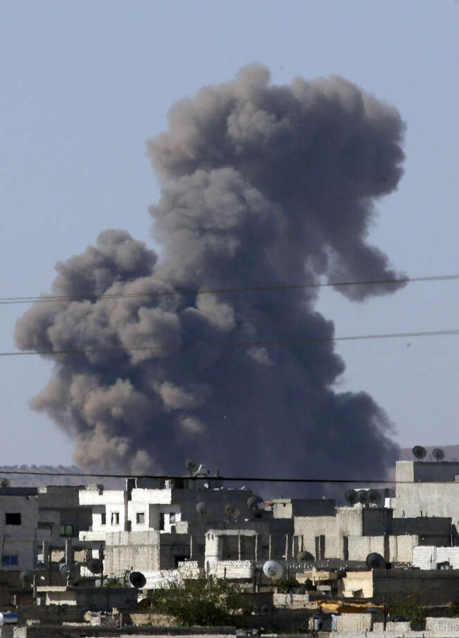 Smoke rises after an airstrike in Kobani, Syria as fighting intensified between Syrian Kurds and the militants of Islamic State group, as seen from Mursitpinar in the outskirts of Suruc, at the Turkey-Syria border, Tuesday, Oct. 7, 2014. Kobani, also known as Ayn Arab and its surrounding areas have been under attack since mid-September, with militants capturing dozens of nearby Kurdish villages. (AP Photo/Lefteris Pitarakis)