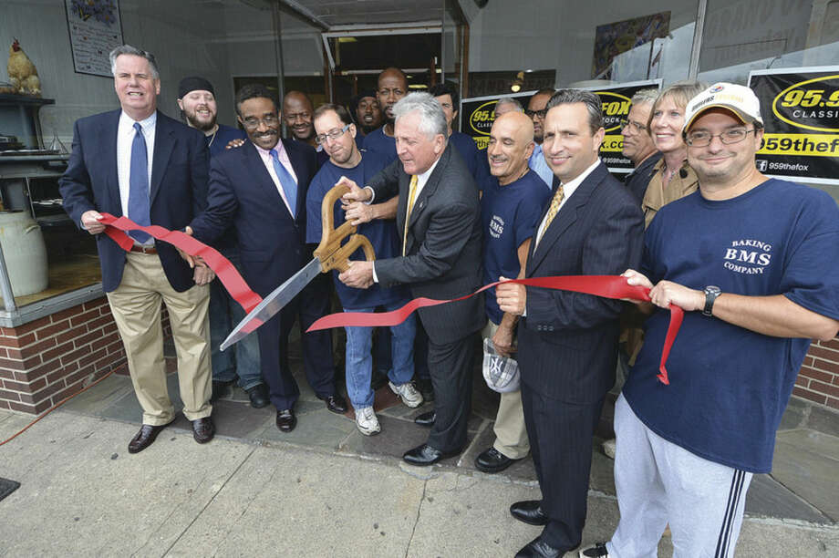 Hour Photo/Alex von Kleydorff Mayor Harry Rilling and Owner Baker Brad Sibilio along with others cut the ribbon in front of BMS Baking Co. in Liberty Square on Thursday