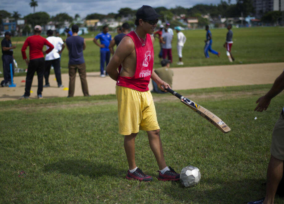 In this Sept. 24, 2014 photo, a cricket player waits his turn to play next to a soccer ball in Havana, Cuba, Monday, Sept. 29, 2014. Without a national tournament, Cuba has amateur tournaments between Cuban teams and teams of students from cricket-playing countries. (AP Photo/Ramon Espinosa)