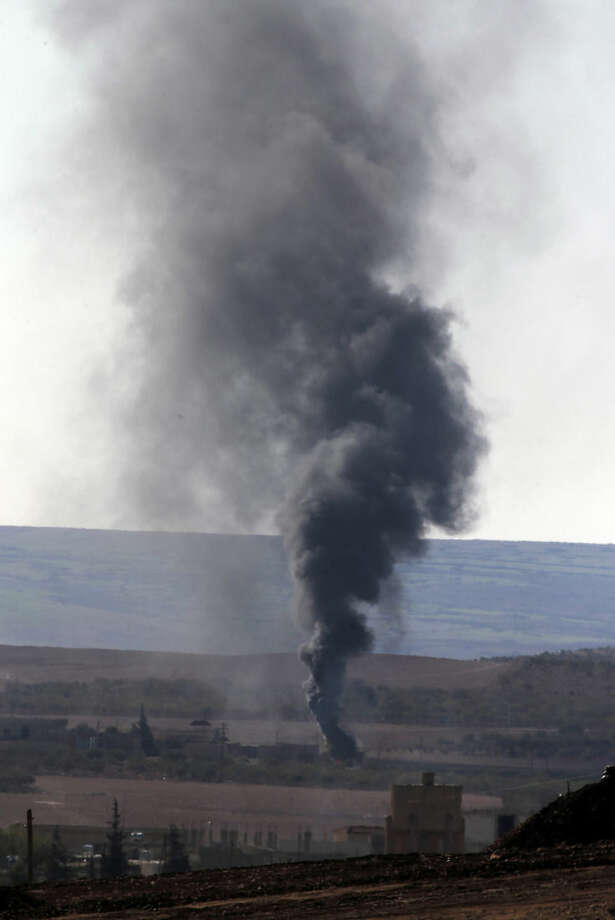 Smoke from a fire rises following a strike in Kobani, Syria, during fighting between Syrian Kurds and the militants of Islamic State group, as seen from a hilltop on the outskirts of Suruc, at the Turkey-Syria border, Tuesday, Oct. 21, 2014. Kobani, also known as Ayn Arab, and its surrounding areas, has been under assault by extremists of the Islamic State group since mid-September and is being defended by Kurdish fighters. (AP Photo/Lefteris Pitarakis)