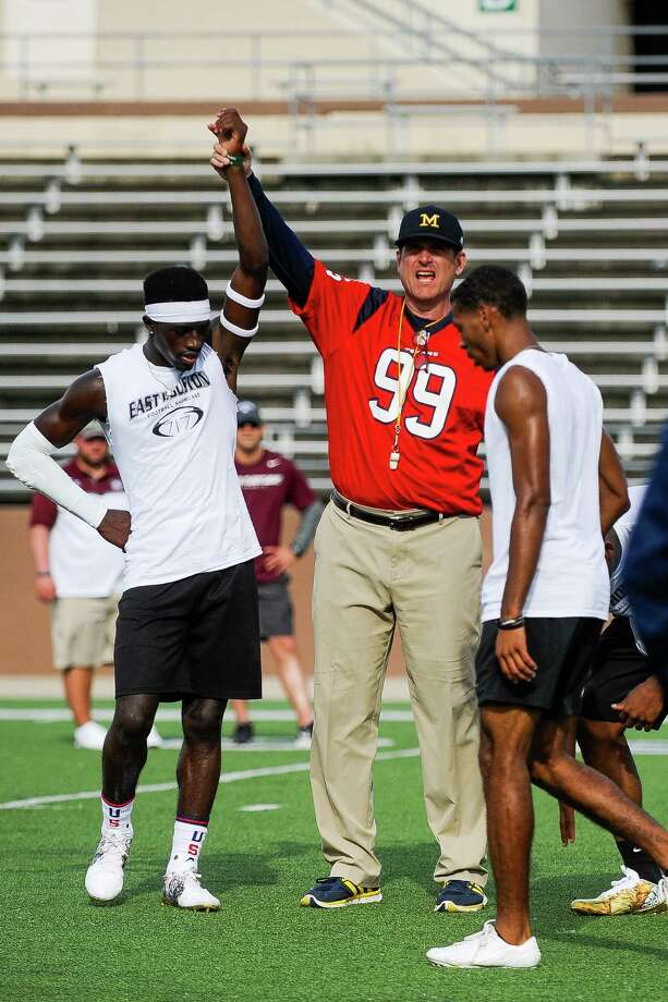 Head football coach at The University of Michigan Jim Harbaugh raises the hand of D'Shawn Jamison after he won a drill at practice at the East Houston Elite Football Showcase Monday, June 13, 2016. Photo: Erin Hull / Erin Hull