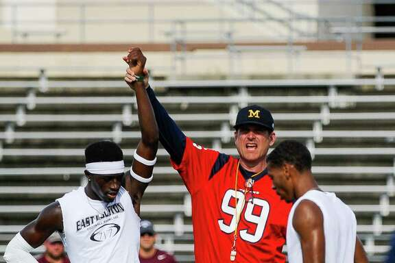 Head football coach at The University of Michigan Jim Harbaugh raises the hand of D'Shawn Jamison after he won a drill at practice at the East Houston Elite Football Showcase Monday, June 13, 2016.