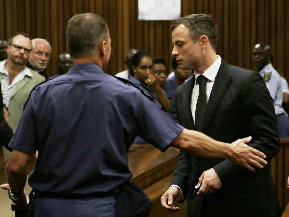 Oscar Pistorius, right, is led out of court in Pretoria, South Africa, Tuesday, Oct. 21, 2014. Pistorius received a five-year prison sentence for culpable homicide by judge Thokozile Masipais for the killing of his girlfriend Reeva Steenkamp last year (AP Photo/Themba Hadebe)