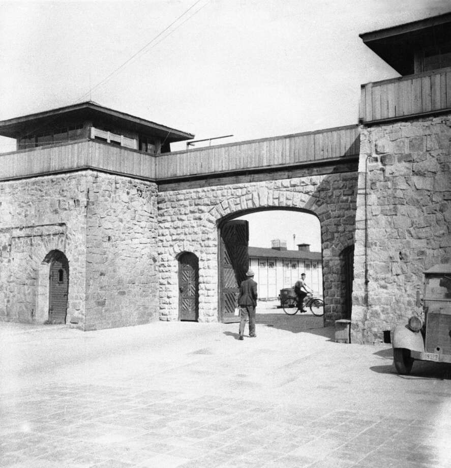 ADVANCE FOR 9:00 P.M. EDT, SUNDAY OCT. 19 AND THEREAFTER - FILE - This July 1945 file photo shows the main gate at Mauthausen concentration camp, near Linz, Austria. An Associated Press investigation found dozens of suspected Nazi war criminals and SS guards collected millions of dollars in Social Security payments after being forced out of the United States. (AP Photo/Lynn Heinzerling, File)