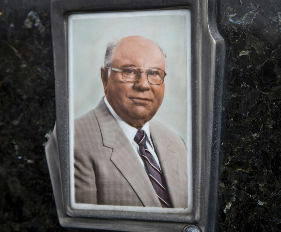 ADVANCE FOR 9:00 P.M. EDT, SUNDAY OCT. 19 AND THEREAFTER - This July 28, 2014, photo shows Jakob Denzinger's portrait on the tombstone of his empty grave in Cepin eastern Croatia. Denzinger is among dozens of death camp guards and suspected Nazi war criminals who collected millions of dollars in Social Security payments despite being forced out of the United States according to an Associated Press investigation. (AP Photo/Darko Bandic)