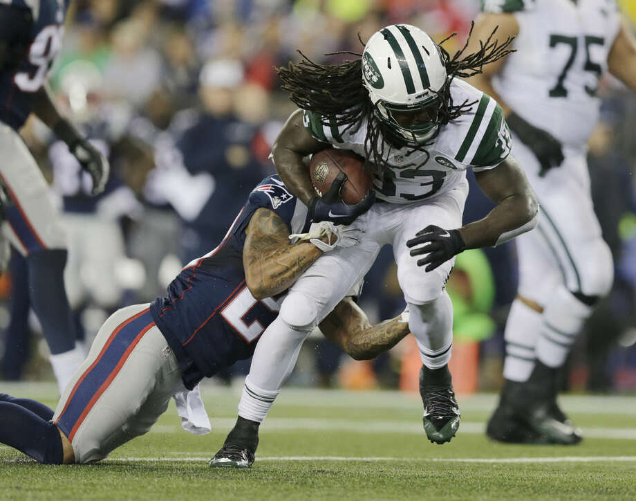 New England Patriots strong safety Patrick Chung, left, tackles New York Jets running back Chris Ivory during the first half of an NFL football game Thursday, Oct. 16, 2014, in Foxborough, Mass. (AP Photo/Charles Krupa)
