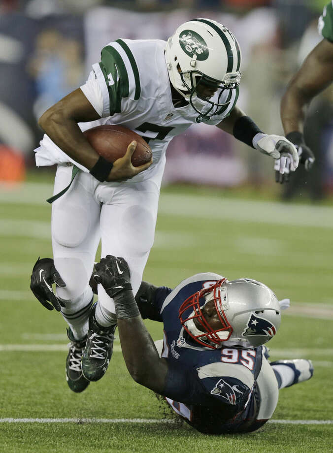 New England Patriots defensive end Chandler Jones, right, tackles New York Jets quarterback Geno Smith during the first half of an NFL football game Thursday, Oct. 16, 2014, in Foxborough, Mass. (AP Photo/Charles Krupa)