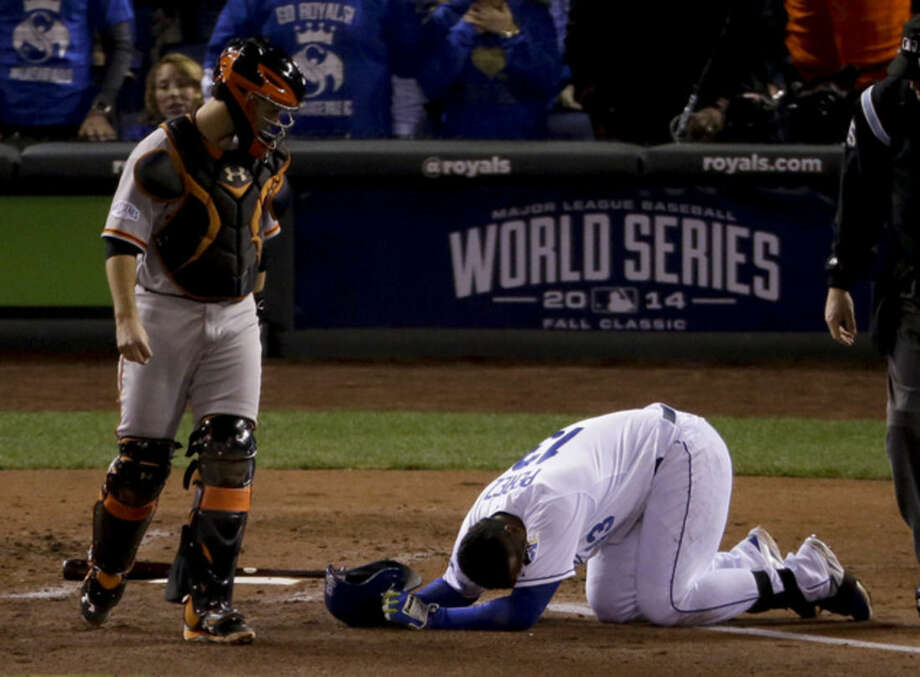 Kansas City Royals Salvador Perez, right, lies on the ground after being hit by pitch by San Francisco Giants Tim Hudson as catcher Buster Posey looks on during the second inning of Game 7 of baseball's World Series Wednesday, Oct. 29, 2014, in Kansas City, Mo. (AP Photo/Charlie Riedel)