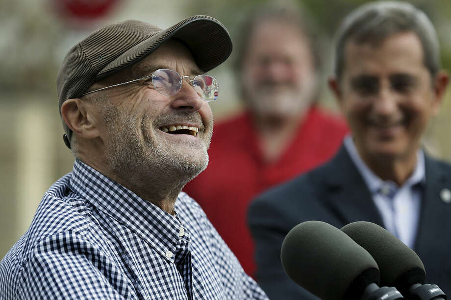 Phil Collins smiles as he speaks to the media with Texas Land Commissioner Jerry Patterson, right, during a news conference on Tuesday, Oct. 28, 2014 in San Antonio. Collins has handed over his vast collection of artifacts related to the Battle of the Alamo and the Texas Revolution to the state of Texas. Collins donated what's considered the world's largest private collection of Alamo artifacts. It includes a fringed leather pouch and a gun used by Davy Crockett and Jim Bowie's legendary knife. (AP Photo/The San Antonio Express-News, Bob Owen) RUMBO DE SAN ANTONIO OUT; NO SALES