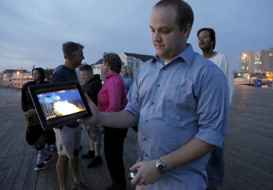 Dave Uhrich, an Ocean City High School physics teacher holds a computer tablet at a gathering of people who were on the Ocean City Boardwalk, in Ocean City, NJ, to view a rocket launched from Virginia that crashed after takeoff Tuesday, Oct., 27, 2014. The unmaned rocket was carry supplies to the International Space Station and contained a science experiment created by the local high school students. (AP Photo/The Press of Atlantic City, Vernon Ogrodnek) MANDATORY CREDIT