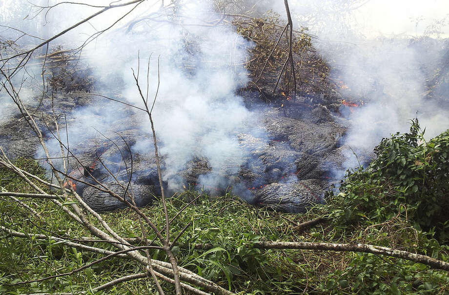 In this Oct. 27, 2014 photo provided by the U.S. Geological Survey, lava flow from Kilauea Volcano that began on June 27 burns through thick vegetation below the pasture downslope of the Pahoa cemetery near the town of Pahoa on the Big Island of Hawaii. Residents of the small town have had weeks to prepare for what's been described as a slow-motion disaster. County officials are making arrangements for those living in the lava's path to be able to watch the lava destroy their homes as a means of closure. (AP Photo/U.S. Geological Survey)