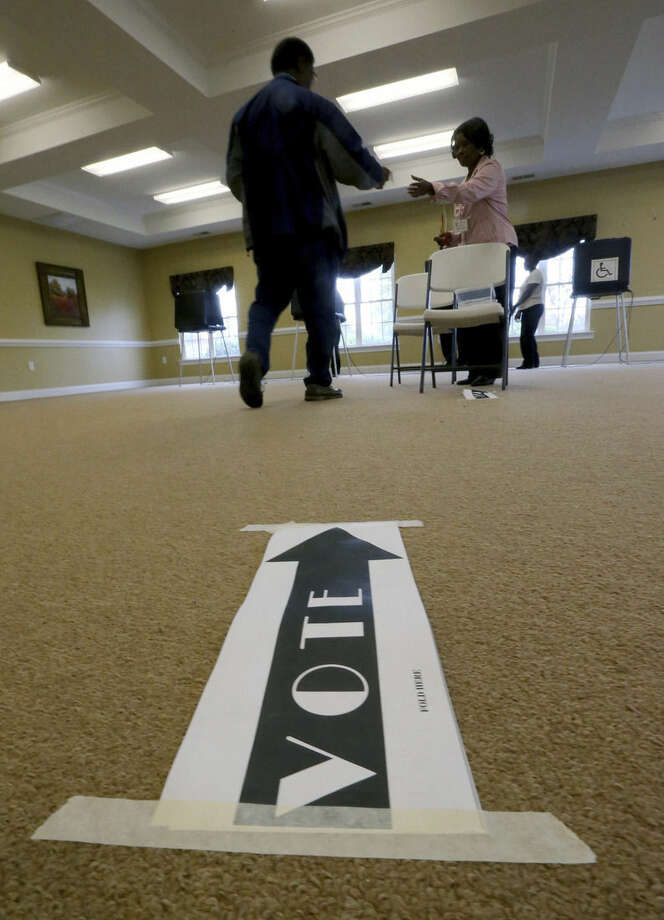 A voter hands his certification to poll worker Elizabeth Lassiter, right, at Precinct 516 in Henrico County on Election Day, Tuesday, Nov. 4, 2014 in Richimond, Va. (AP Photo/Richmond Times-Dispatch, Bob Brown)