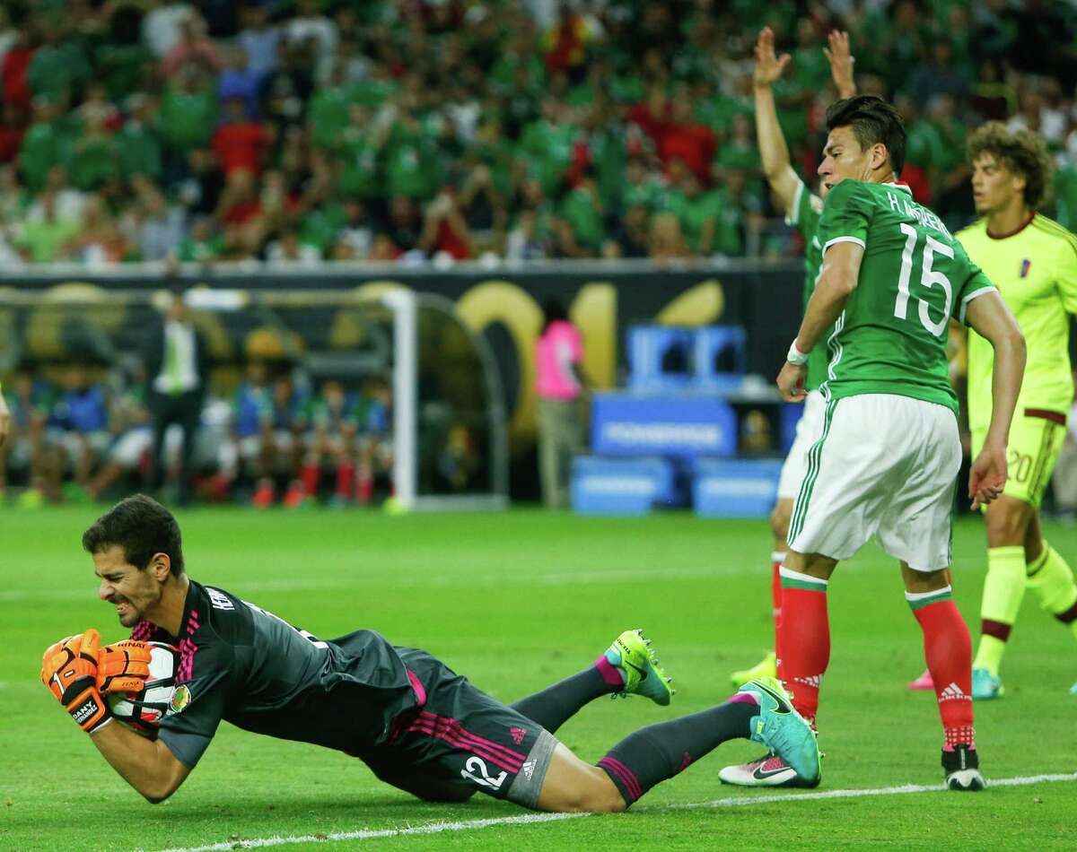 Venezuela goalkeeper Dani Hernandez (12) dives to the ground past Mexico's Hector Moreno (15) after making a leaping save during the second half of a Copa America Centenario group C soccer match on Monday, June 13, 2016, in Houston. The match ened in a 1-1 draw.