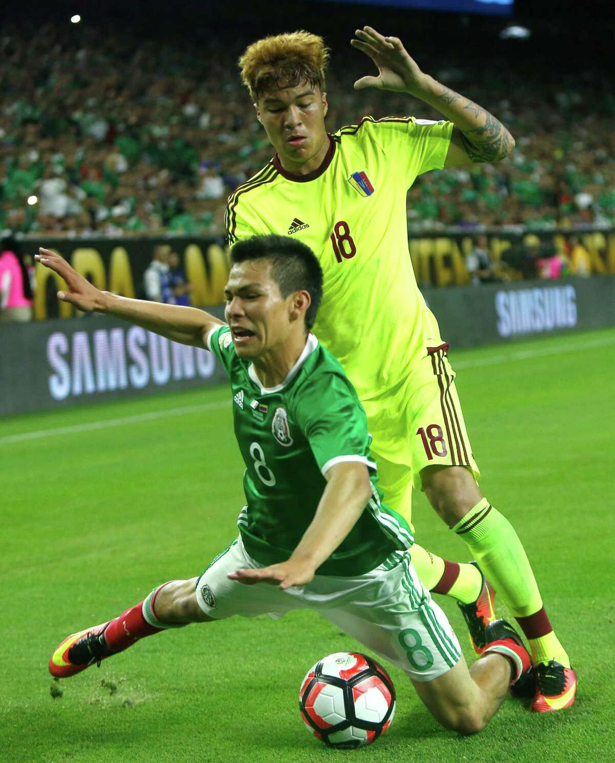 Mexico midfielder Hirving Lozano (8) is knocked to the field by Venezuela midfielder Adalberto Penaranta (18) as they chase the ball toward the end line during the second half of a Copa America Centenario group C soccer match on Monday, June 13, 2016, in Houston. The match ened in a 1-1 draw.