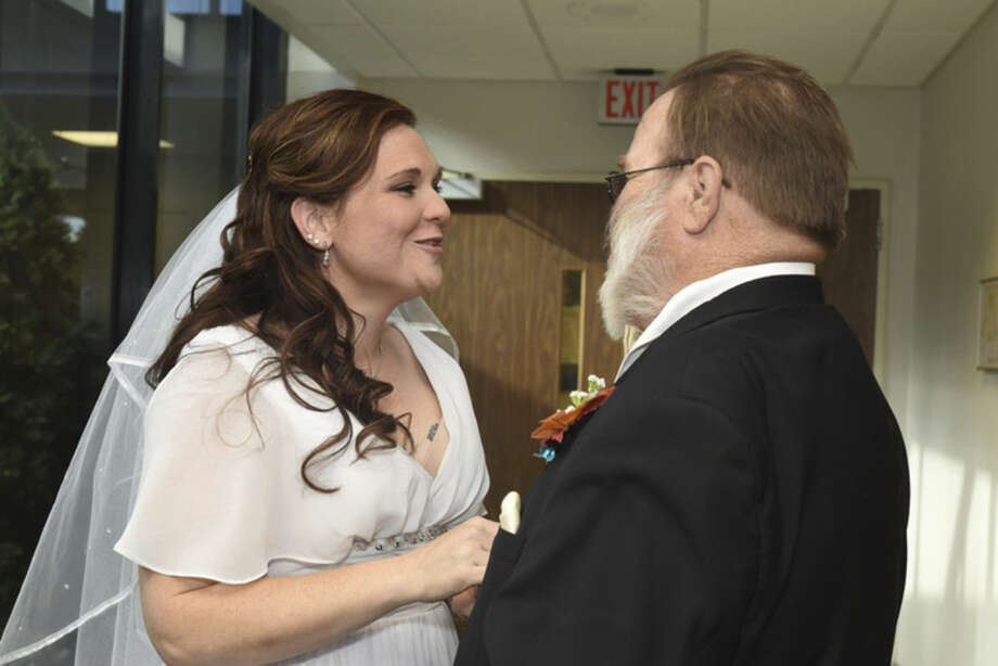 In this Saturday, Nov. 1, 2014 photo, bride Crysta Danaher fixes her father, Joe Danaher's, tie before her wedding at the Wyandotte Henry Ford Hospital in Wyandotte, Mich. Crysta Danaher and Bill Anderson met at the hospital 3 years before during a pre-bariatric counseling. They lost over 200 pounds together. The couple decided to get married in the same room they met inside the Wyandotte Henry Ford Hospital. (AP Photo/Detroit Free Press, Tanya Moutzalias)