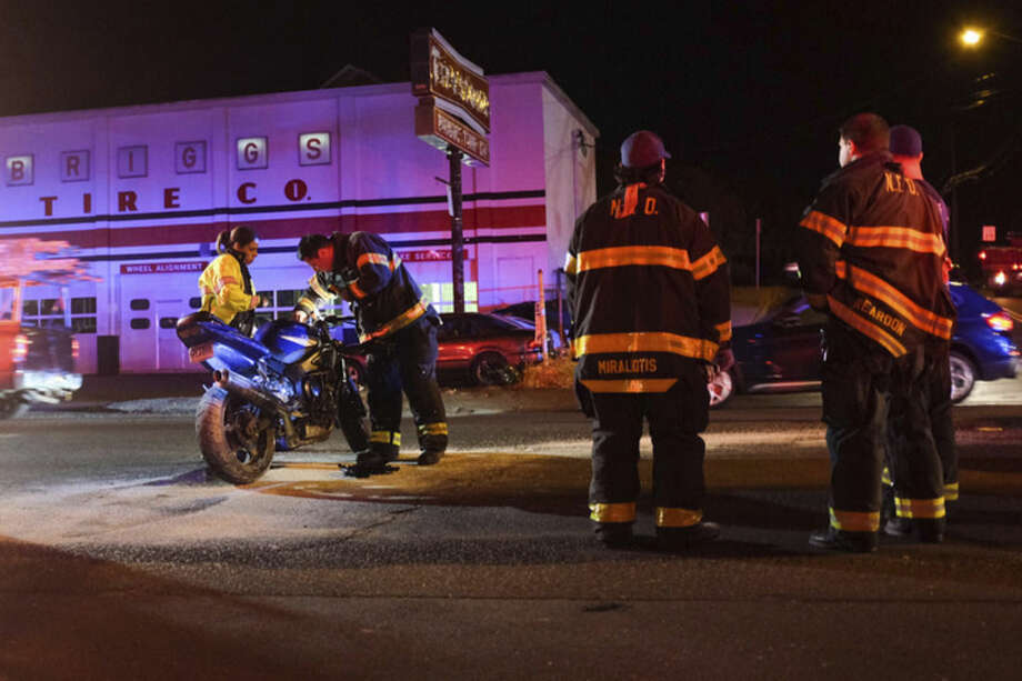 Norwalk Police and Fire officials respond to the scene where a motorcyclist was struck by a white pickup truck on the corner of Stuart and Connecticut Avenue Monday night. Witnesses said the motorcyclist was taken to the hospital, but looked to be in stable condition.