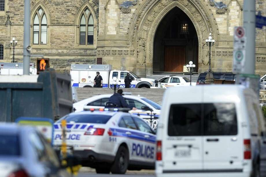 Police converge on Parliament Hill in Ottawa on Wednesday Oct. 22, 2014. A soldier standing guard at the National War Memorial was shot by an unknown gunman and people reported hearing gunfire inside the halls of Parliament. Prime Minister Stephen Harper was rushed away from Parliament Hill to an undisclosed location, according to officials. (AP Photo/The Canadian Press, Adrian Wyld)