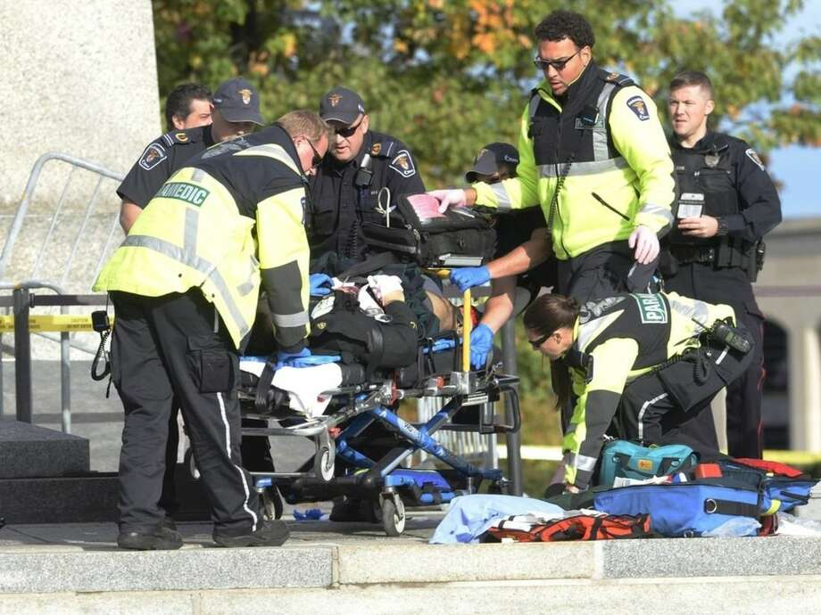 Police and paramedics tend to a soldier shot at the National Memorial near Parliament Hill in Ottawa on Wednesday Oct. 22, 2014. The soldier standing guard at the National War Memorial was shot by an unknown gunman and people reported hearing gunfire inside the halls of Parliament. Prime Minister Stephen Harper was rushed away from Parliament Hill to an undisclosed location, according to officials. (AP Photo/The Canadian Press, Adrian Wyld)