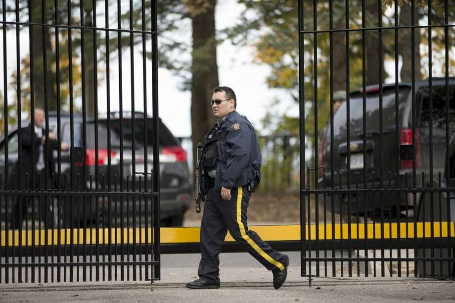 An armed RCMP officer stands guard at 24 Sussex Dr., the official residence of the Prime Minister, on Wednesday, Oct. 22, 2014. A soldier standing guard at the National War Memorial has been shot by an unknown gunman and there have been reports of gunfire inside the halls of Parliament. (AP Photo/The Canadian Press, Justin Tang)