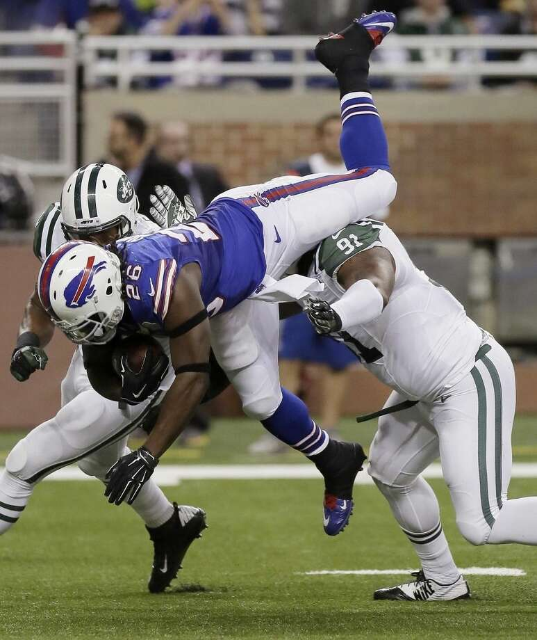 Buffalo Bills running back Anthony Dixon (26) is upended by New York Jets defensive end Sheldon Richardson (91) during the first half of an NFL football game in Detroit, Monday, Nov.24, 2014. (AP Photo/Duane Burleson)
