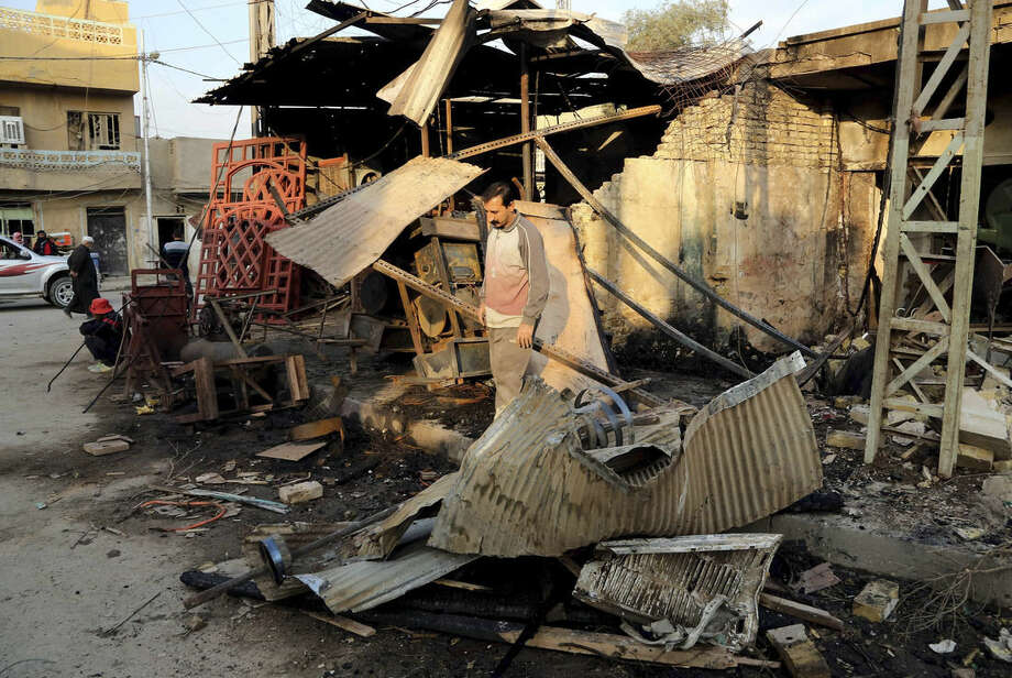 FILE - In this file photo taken on Saturday, Nov. 15, 2014, civilians inspect the site of Friday's car bomb in Baghdad Goraya neighborhood, Iraq, The government is now trying to revamp security measures, moving away from reliance on ubiquitous concrete blast walls and police checkpoints. Instead, the plan is to beef up police intelligence units that have gone understaffed and underfunded since the fall of Saddam Hussein. (AP Photo/Karim Kadim, File)