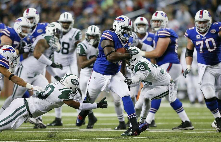 Buffalo Bills running back Anthony Dixon pulls away from the New York Jets defense for a 30-yard touchdown during the second half of an NFL football game in Detroit, Monday, Nov.24, 2014. (AP Photo/Rick Osentoski)