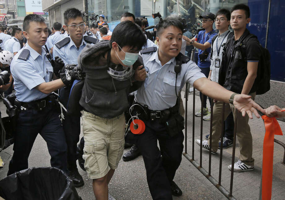Police officers arrest a protester as they clear a protest site after warning the crowd that they would start enforcing the court-ordered clearance at an occupied area in Mong Kok district of Hong Kong Wednesday, Nov. 26, 2014. Hong Kong authorities cleared street barricades from a pro-democracy protest camp in the volatile Mong Kok district for a second day Wednesday after a night of clashes. (AP Photo/Vincent Yu)