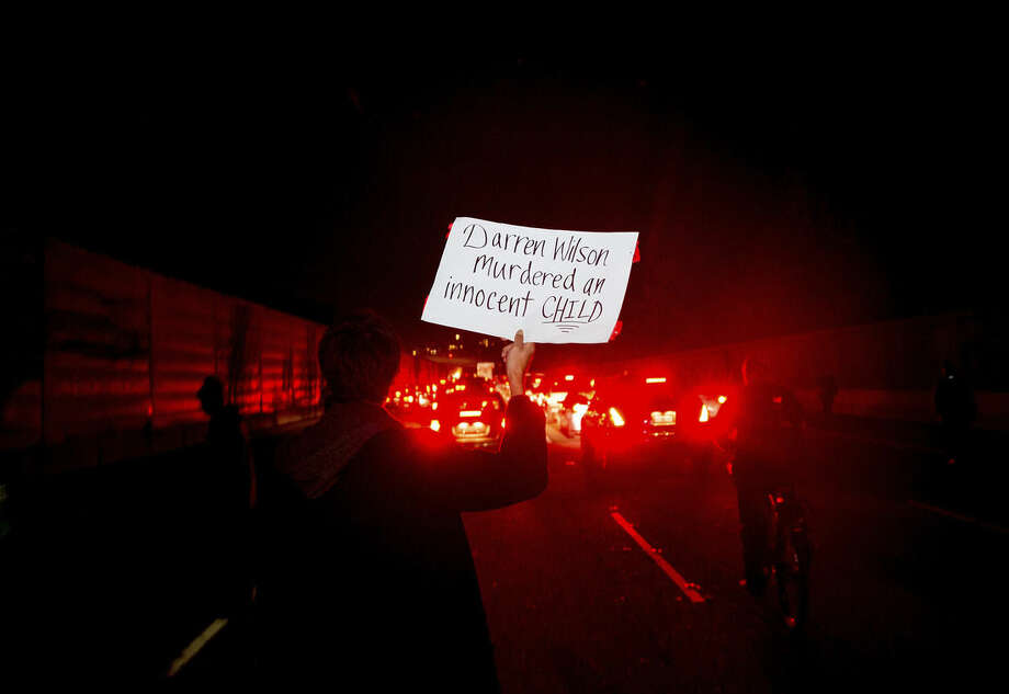 Dante Kaleo holds a protest sign while marching on Interstate 580 in Oakland, Calif., on Monday, Nov. 24, 2014, after the announcement of the grand jury decision not to indict Ferguson police officer Darren Wilson in the fatal shooting of Michael Brown, an unarmed 18-year-old. Several thousand protesters marched through Oakland with some shutting down freeways multiple times, burning refuse and breaking windows on a news van. (AP Photo/Noah Berger)