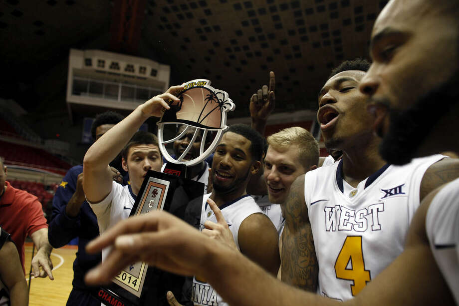 West Virginia players celebrate with their trophy after winning the NCAA college basketball Puerto Rico Tip-off tournament following their victory over UConn in San Juan, Puerto Rico, Sunday, Nov. 23, 2014. (AP Photo/Ricardo Arduengo)