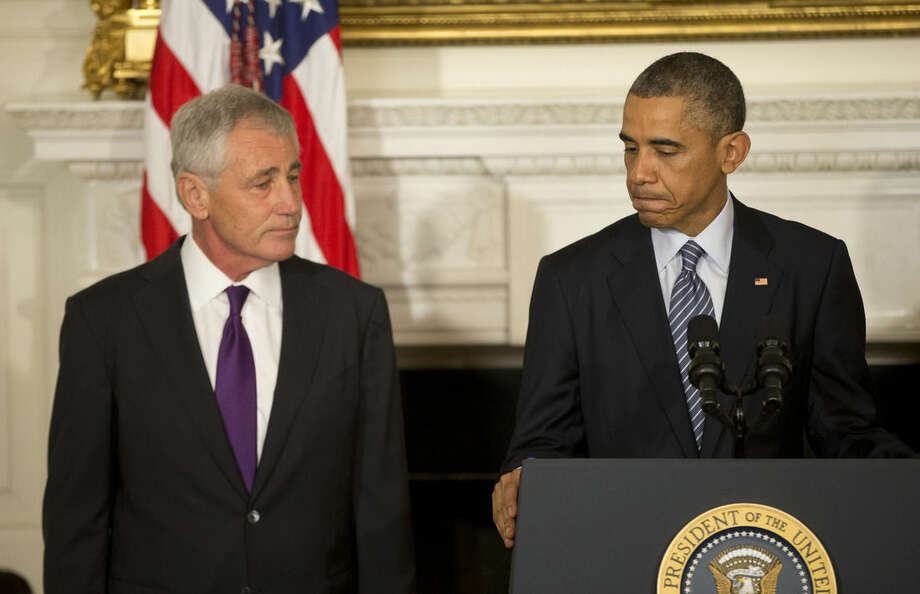 President Barack Obama, standing with Defense Secretary Chuck Hagel, talks about Hagel's resignation during an event in the State Dining Room of the White House in Washington, Monday, Nov. 24, 2014. Hagel is stepping down under pressure from Obama's Cabinet, senior administration officials said Monday, following a tenure in which he has struggled to break through the White House's insular foreign policy team. (AP Photo/Pablo Martinez Monsivais)
