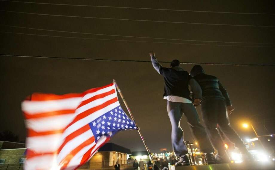 Protestors demonstrate along a stretch of road where violent protests occurred following the August shooting of unarmed black teenager by a white police officer, Saturday, Nov. 22, 2014, in Ferguson, Mo. Ferguson and the St. Louis region are on edge in anticipation of the announcement by a grand jury whether to criminally charge officer Darren Wilson in the killing of 18-year-old Michael Brown. (AP Photo/David Goldman)