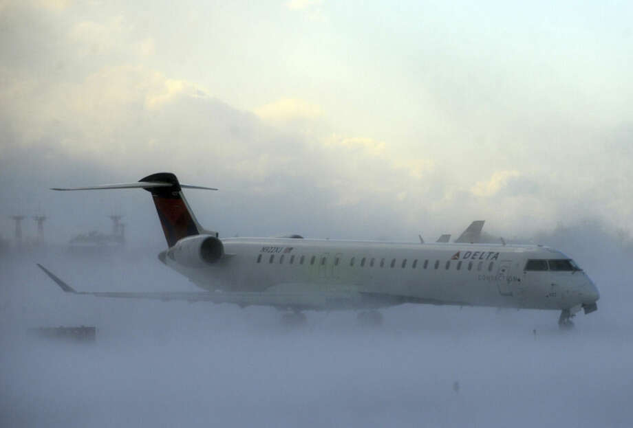 Lake-effect snow storm with freezing temperatures affected travel, like this plane that negotiated its way through the snow at Buffalo Greater International Airport, in Buffalo, N.Y. Tuesday, Nov. 18, 2014. Temperatures fell to freezing or below at recording stations in all 50 states on Tuesday morning, from the highest elevations in the mountains of Hawaii to the snow-paralyzed Buffalo area in New York. (AP Photo/Gary Wiepert)