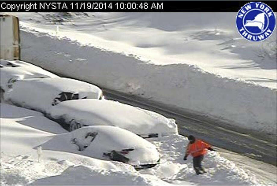 In this photo from a surveillance camera operated by the New York State Thruway Authority, a person climbs through piles of snow next to abandoned vehicles on the Thruway, near Lackawanna, N.Y., Wednesday, Nov. 19, 2014. A 132-mile stretch of the state Thruway in western New York remains closed as authorities continue their efforts to rescue motorists stranded on a Buffalo-area section of the highway. (AP Photo/New York State Thruway Authority)