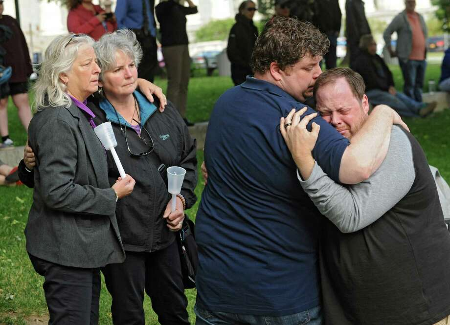 Beth Bochum of Schodack Landing, left, stands with her wife Betsy Soares as Chad Radock of Saratoga Springs, second from right, hugs his emotional husband Jeremy Buechner during a vigil held for the victims of the Orlando massacre at West Capitol Park on Monday, June 13, 2016 in Albany, N.Y. (Lori Van Buren / Times Union) Photo: Lori Van Buren / 40036950A