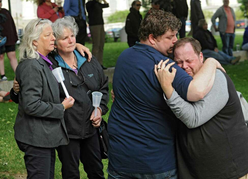 Beth Bochum of Schodack Landing, left, stands with her wife Betsy Soares as Chad Radock of Saratoga Springs, second from right, hugs his emotional husband Jeremy Buechner during a vigil held for the victims of the Orlando massacre at West Capitol Park on Monday, June 13, 2016 in Albany, N.Y. (Lori Van Buren / Times Union)