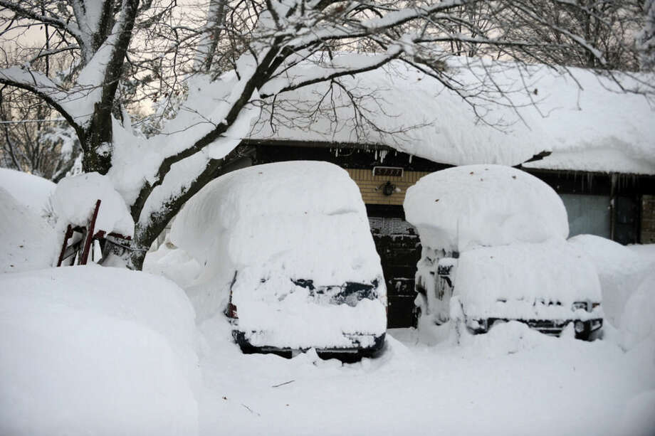 Cars with snow atop the roofs sit idle at this home on Broadway in Lancaster, N.Y. Wednesday, Nov. 19, 2014. A ferocious storm dumped massive piles of snow on parts of upstate New York, trapping residents in their homes and stranding motorists on roadways, as temperatures in all 50 states fell to freezing or below. (AP Photo/Gary Wiepert)