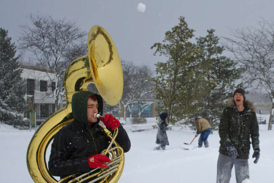 Gabriel Ellis throws a snowball at Lukas Schroeder as he plays the tuba on the Grand Valley State University campus, in Allendale, Mich., Tuesday, Nov. 18, 2014. Lake-effect storms in Michigan produced gale-force winds and as much as 18 inches of snow, and canceled several flights at the Grand Rapids airport. (AP Photo/The Grand Rapids Press, Joel Bissell) ALL LOCAL TELEVISION OUT; LOCAL TELEVISION INTERNET OUT