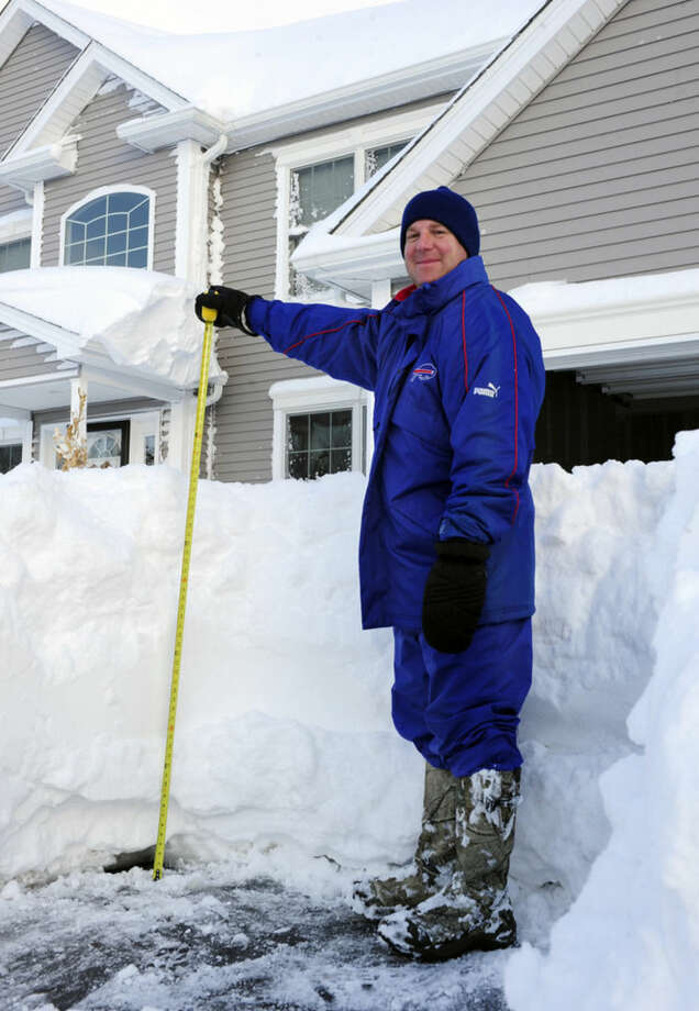 Art Hauret pauses after he measures the nearly four foot accumulation of snow in his driveway on Summerfield Drive in Lancaster, N.Y. Wednesday, Nov. 19, 2014. A ferocious storm dumped massive piles of snow on parts of upstate New York, trapping residents in their homes and stranding motorists on roadways, as temperatures in all 50 states fell to freezing or below. (AP photo/Gary Wiepert)