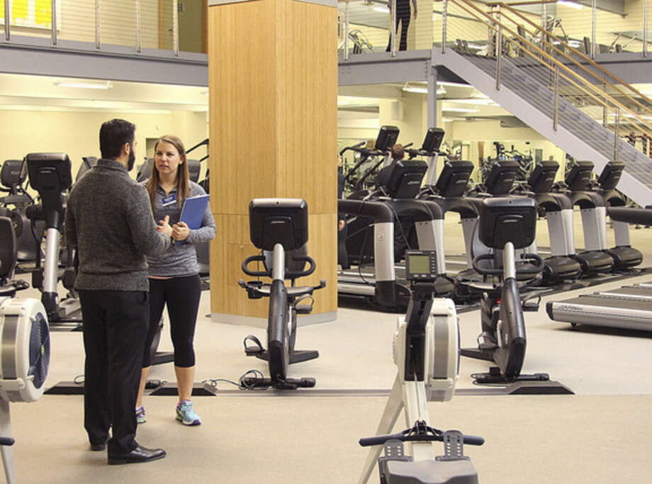Hour photos/Chris BosakA staff member at Chelsea Piers Connecticut in Stamford gives a tour of the new fitness center at the facility during an open house on Wednesday evening. Below, David Tewksbury, executive vice president of Chelsea Piers, and Greta Wagner, executive director of Chelsea Piers CT stand in the facility's new fitness center.