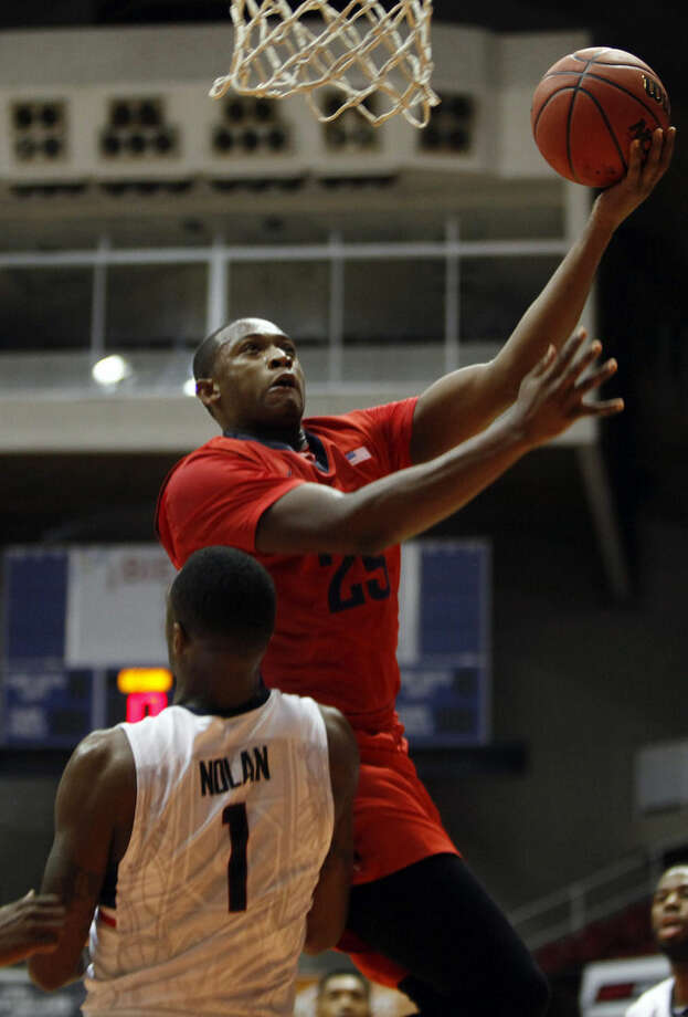 Dayton forward Kendall Pollard, top, goes to the basket against UConn forward Phillip Nolan during a NCAA college basketball game in San Juan, Puerto Rico, Friday, Nov. 21, 2014. (AP Photo/Ricardo Arduengo)