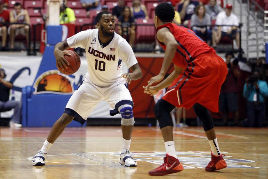 UConn guard Sam Cassell Jr., left, controls the ball under pressure from Dayton guard Darrell Davis during a NCAA college basketball game in San Juan, Puerto Rico, Friday, Nov. 21, 2014. (AP Photo/Ricardo Arduengo)